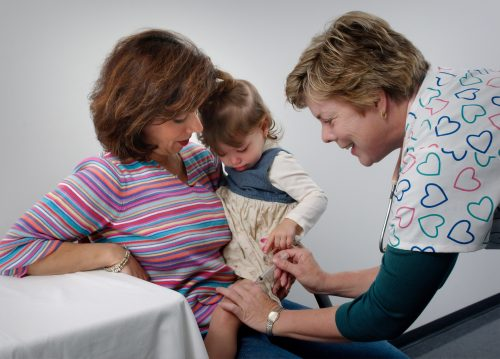 This photograph showed a young child being cradled by her mother, while she was receiving an intramuscular vaccination in her left thigh muscle. Notice that the nurse had immobilized the young girl's leg using her left hand.